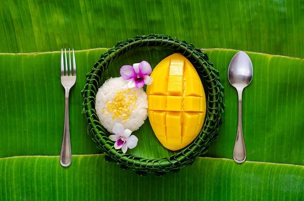 Тайский десерт - липкий рис с манго на тарелке из банановых листьев вилкой и ложкой на фоне банановых листьев.