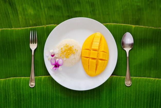 Тайский десерт - липкий рис с манго на белой тарелке вилкой и ложкой на фоне банановых листьев.