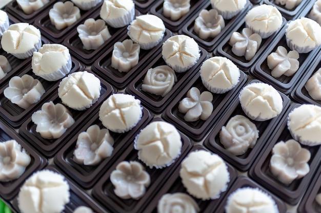 タイのデザート、白いマフィンカップケーキ、またはコットンウールのケーキとバナナのデザートを組み合わせた、甘い味わいをダークブラウンのトレイに置きます。