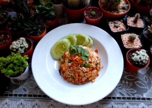선인장과 다육 식물 배경에 신선한 얇게 썬 오이를 곁들인 태국식 계란 볶음밥