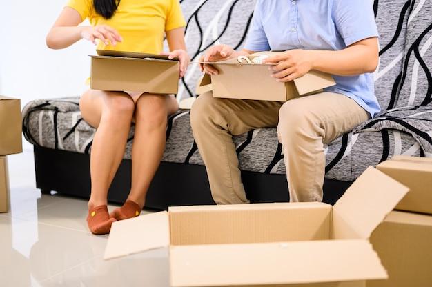 タイの起業家のカップルが荷造りしています。オリーンショッピングと宅配。自宅での中小企業ビジネスのためのロックダウンと自己検疫。