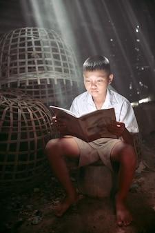 태국 농부의 아이들이 닭 농장에서 책을 읽고 있습니다.