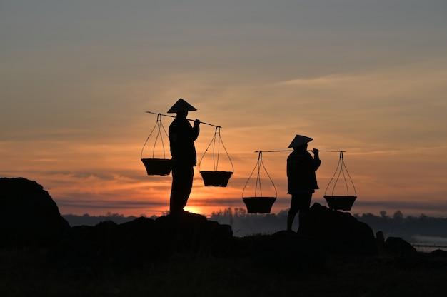 태국 농부들은 해가지기 전에 집에 갈 준비를하기 위해 바구니를 들고 있습니다. 실루엣 농부. 실루엣 빛.