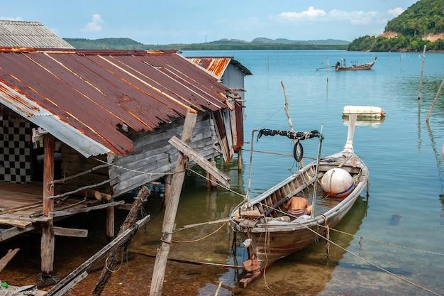 Длинная лодка для тайской рыбалки рядом со старой ржавой хижиной рыбака