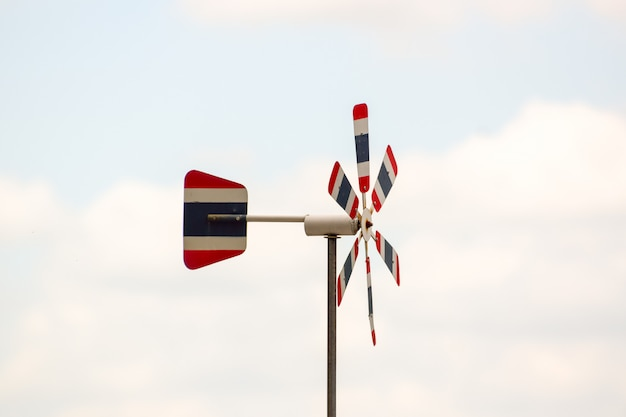 Thai flag wind turbine, blurred natural sky color, the wind blows through, causing the propeller to rotate, free space in the image