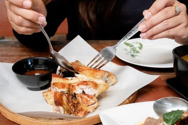 タイ料理のコンセプトアジアの女性は、スプーンとフォークを使って、白い紙にローストチキンをディップソースでスライスして食べています。