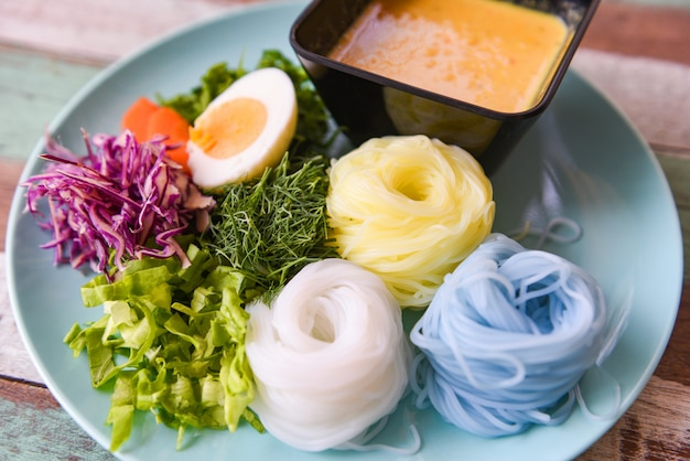 タイ料理美味しくて美味しい料理/カラフルなライスヌードルまたはタイライス春雨ヌードルと魚のカレーカレースープソースと野菜のプレート木製テーブル