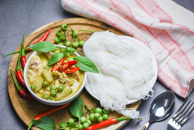 タイ料理グリーンカレーチキンのスープボウルとタイ米麺春雨成分ハーブ野菜-テーブルの上のアジア料理