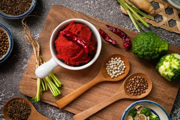 タイの食材-コリアンダーの根、コリアンダーの種、クミン、コブミカンの皮、乾燥唐辛子、白胡椒などのコンディメットが付いた木製のまな板のスパイシーなカレーペースト