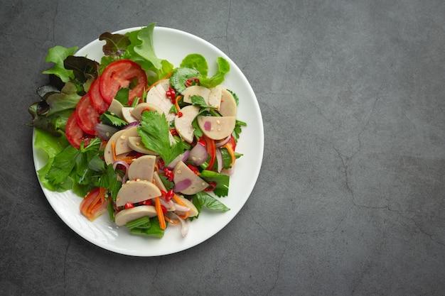 Тайская еда; смешанный острый салат из белых свиных колбасок или yum moo yor