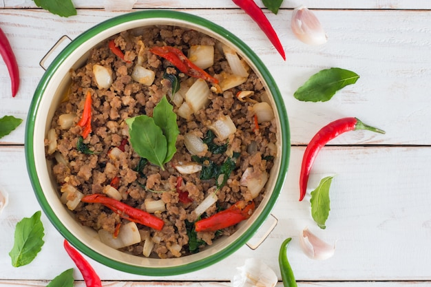 Thai food name pad ka prao,top view image of stir-fried pork with basil leaves on white wood table
