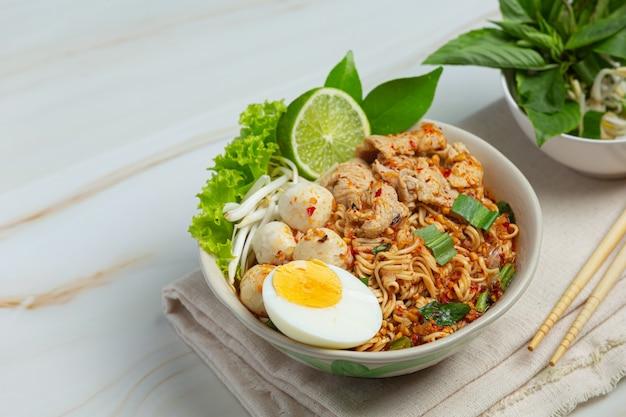 Cibo thailandese. bollire le tagliatelle piccanti con carne di maiale e bollire l'uovo