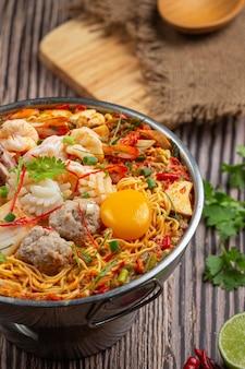 タイ料理。鍋にシーフードと豚肉を入れてスパイシーに煮込んだ麺