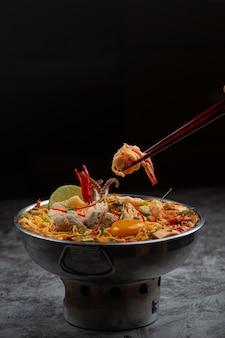 Тайская еда. лапша острая отварная с морепродуктами и свининой в горшочке
