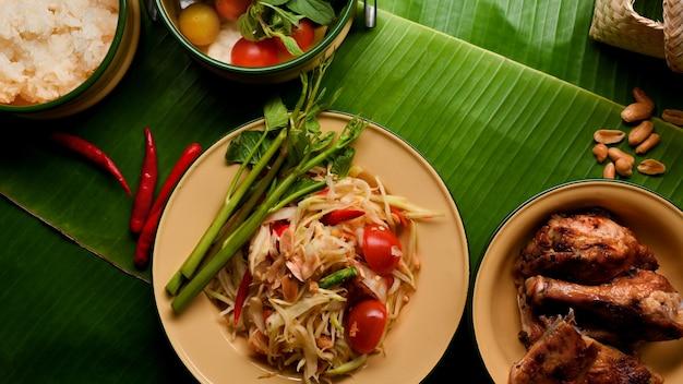 タイ料理のパパイヤサラダソムタムは、バナナの葉の背景にタイ風グリルチキンともち米を添えて