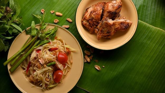 バナナの葉の背景にタイ風グリルチキンを添えたタイ料理パパイヤサラダソムタム