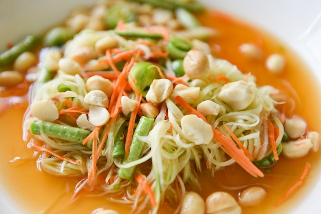 Thai food papaya salad with macadamia nuts on top on white plate