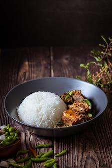Thai food, rice topped with stir fried basil and pork bone.