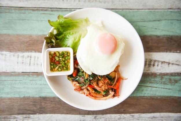 タイ料理の野菜とチリソースのスパイシー揚げレシピ。チャーハンと豚肉の炒めご飯の上にバジルと卵焼き