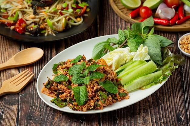 Cibo tailandese; carne di maiale macinata piccante servire con contorni