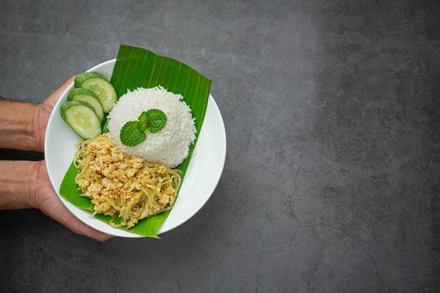 Тайское блюдо stir fried egg with papaya, приготовленное с рисом