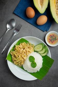Cibo tailandese mescolare l'uovo fritto con papaia cotta servire con riso