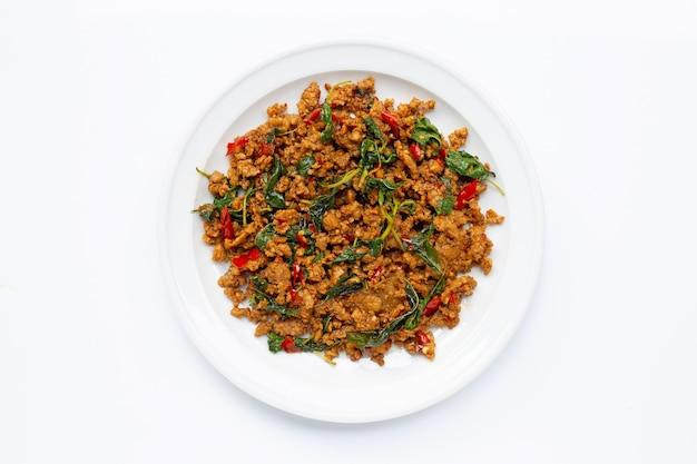 Тайская еда. жареный свиной фарш с листьями базилика на белом.