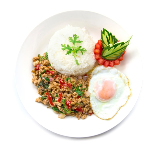 Thai food stir-fried pork spicy and basil served with rice and fried egg and tomato cucumber