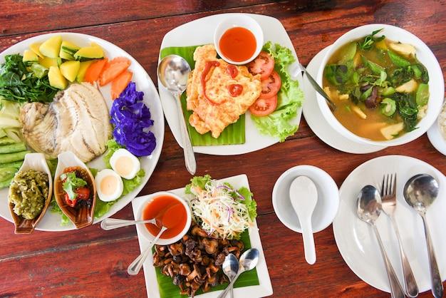 タイ料理のトップビュー、プレートメニューの木製のテーブル設定でアジア料理