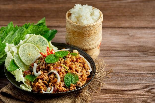 Il cibo tailandese con carne di maiale macinata piccante serve con contorni e riso appiccicoso