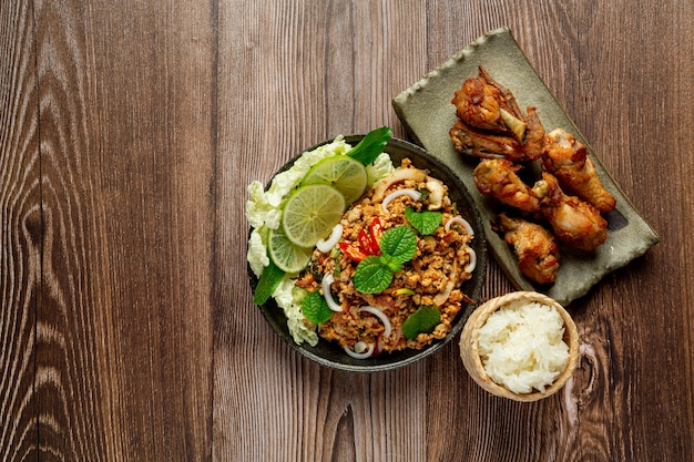 매콤한 다진 돼지 고기를 곁들인 태국 음식에는 찹쌀과 프라이드 치킨이 함께 제공됩니다.
