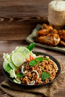 Il cibo tailandese con carne di maiale macinata piccante serve con riso appiccicoso e pollo fritto