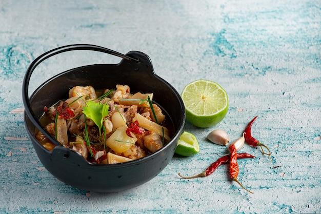 검은 그릇에 매운 돼지 다리 수프와 태국 음식
