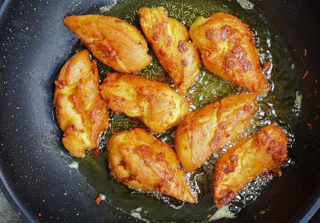 팬에 심황과 기름을 얹은 태국식 프라이드 치킨
