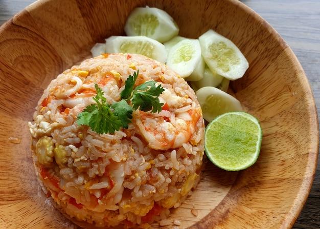 Тайский жареный рис с креветками, нарезанным лаймом и свежим нарезанным огурцом в деревянной миске