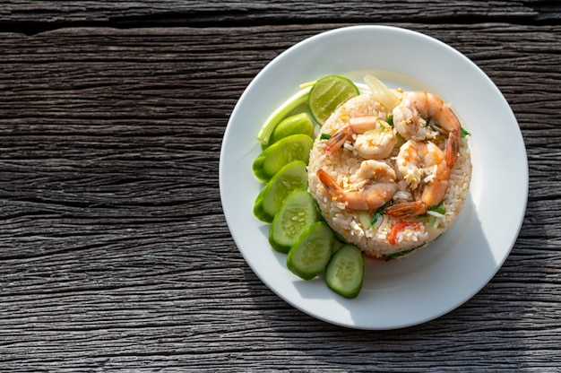 Thai fried rice with prawns and vegetables on wooden table Premium Photo