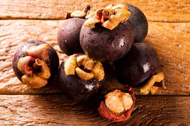 Тайские фрукты: мангостин - королева фруктов. органические фрукты в корзине. свежие мангустины на деревянном столе. выборочный фокус.