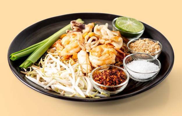 エビのタイ焼きそば、パッタイはタイの有名な屋台の食べ物で、クリーム色の背景に分離されています