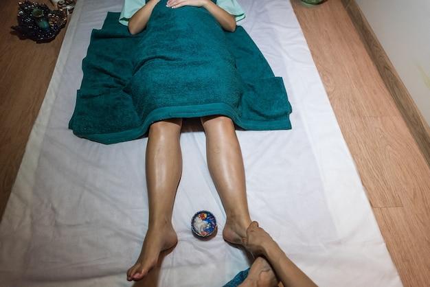 Тайская девушка делает массаж ног европейской девушке в спа салоне