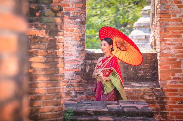 タイの女の子は、歴史的な公園でタイの衣装を身に着けている