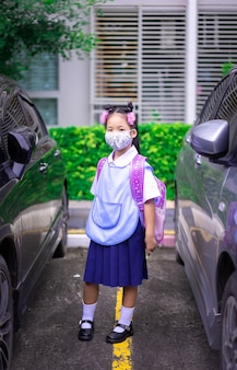 Thai girl student wearing a mask against coronavirus and pm 2.5 air pollution before going to school