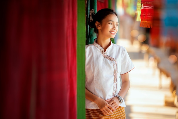 Thai girl in traditional lanna costume travel in  lamduan woven cloth