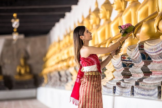 Thai girl in traditional thai costume hand holding lotus in thai temple, identity culture of thailand.
