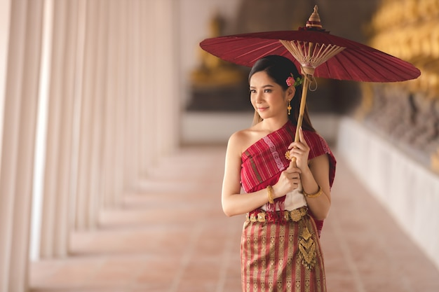 Thai girl in traditional thai costume with red umbrella in thai temple, identity culture of thailand.