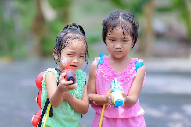 タイの時代のドレスとソンクラン祭りで水鉄砲を遊んでいるタイの女の子の子供たち