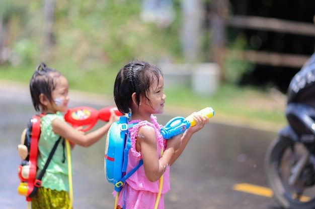 Thai girls children playing water guns in songkran festival with thai period dress