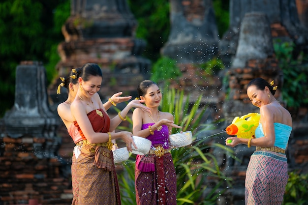 Thai girls in thai traditional dress splashing water during festival songkran festival, ayutthaya, thailand.
