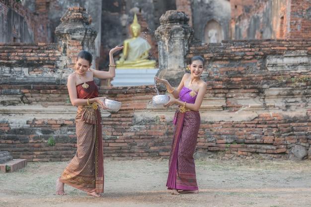 Thai girls in thai traditional dress splashing water during festival songkran festival, ayutthaya, thailand.