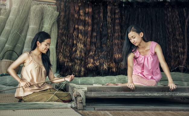 Thai girls working textiles with the papyrus the mat.