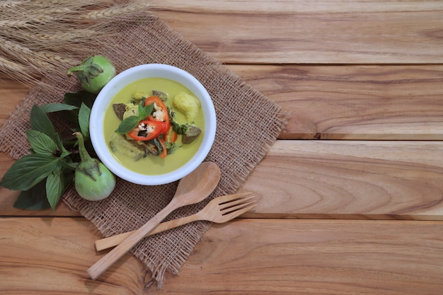 Thai green curry soup on a wooden table with ingredients
